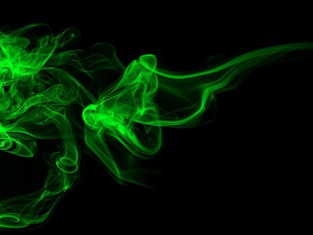 Groene rooksamenvatting op zwarte backgroud, duisternisconcept