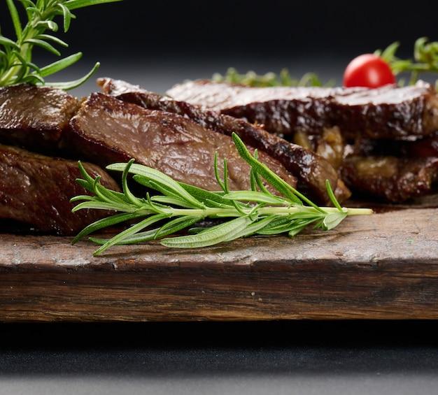Groene rozemarijntak op een achtergrond van gebakken rundvleesplakken op een bruin houten bord