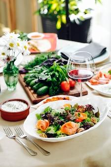 Groene sala met kruiden en een glas rode wijn.