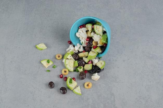 Groene salade in een blauw kopje met zwarte olijven en appels