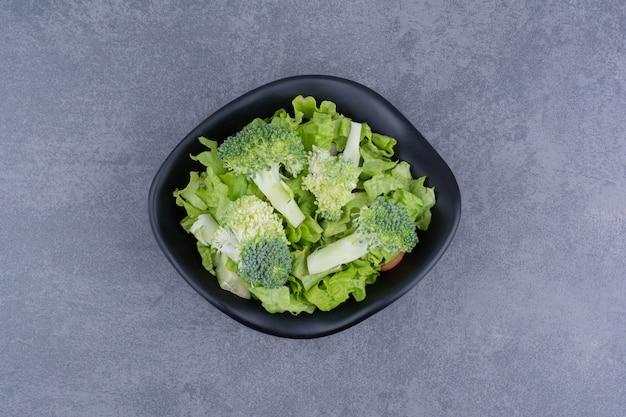 Groene salade in een bord op blauwe ondergrond