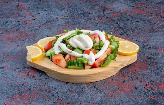 Groene salade in een houten schotel met mayonaisesaus.