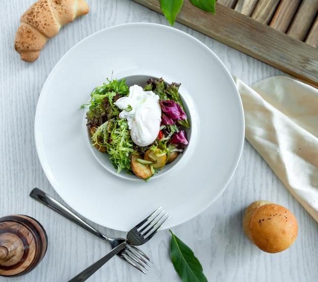 Groene salade met aardappeltjes op de witte plaat