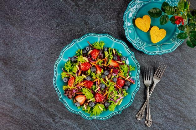 Groene salade met bessen en kipnuggets en roos valentijnsdag concept.
