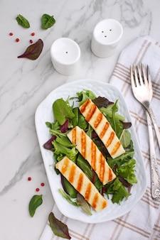 Groene salade met gebakken halloumi kaas in een witte plaat op een marmeren tafel, bovenaanzicht