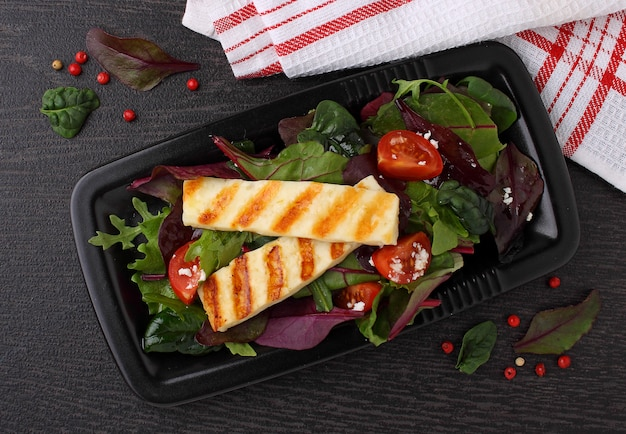 Groene salade met gebakken halloumi kaas op een zwarte plaat