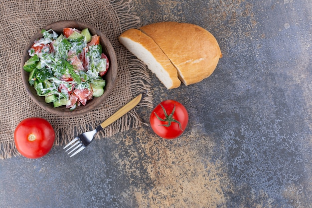 Groene salade met gehakte tomaten, kruiden en komkommer gemengd met zure room