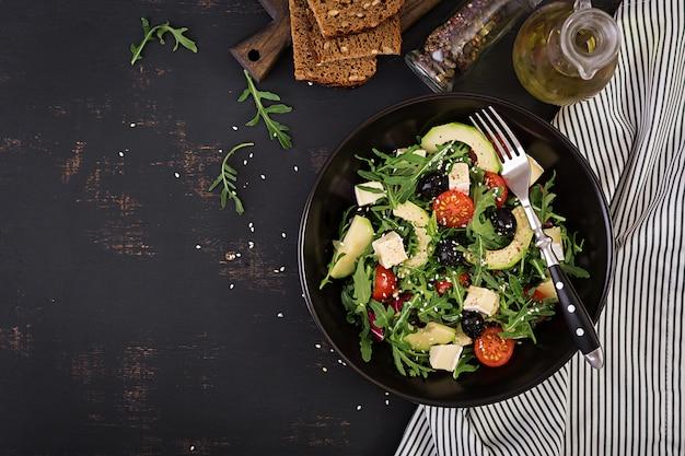 Groene salade met gesneden avocado, cherry tomaten, zwarte olijven en kaas