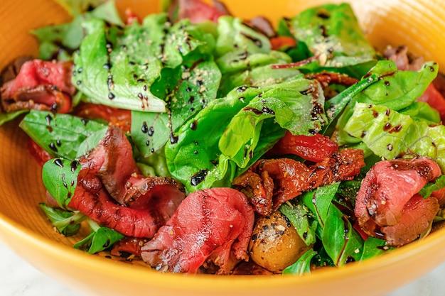 Groene salade met gesneden rosbief, zongedroogde tomaten en aardappelen