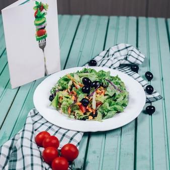 Groene salade met kruiden, zwarte olijven en tomaat.