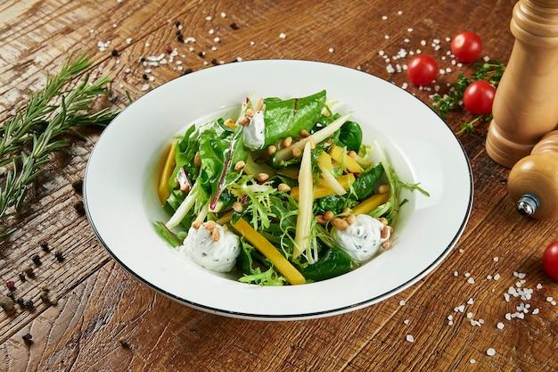 Groene salade met mango en pittige, boerderij geitenkaas en sla in een witte kom op een houten oppervlak in een compositie met kruiden. close up bekijken