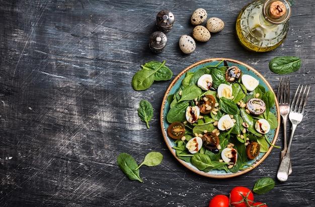 Groene salade met spinazie tomaten kwarteleitjes en pijnboompitten op zwart