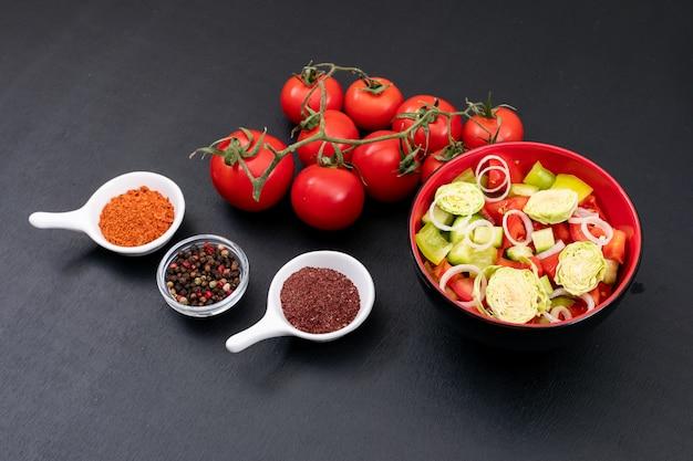 Groene salade met tomaat en verse groenten die op zwarte oppervlakte worden geïsoleerd