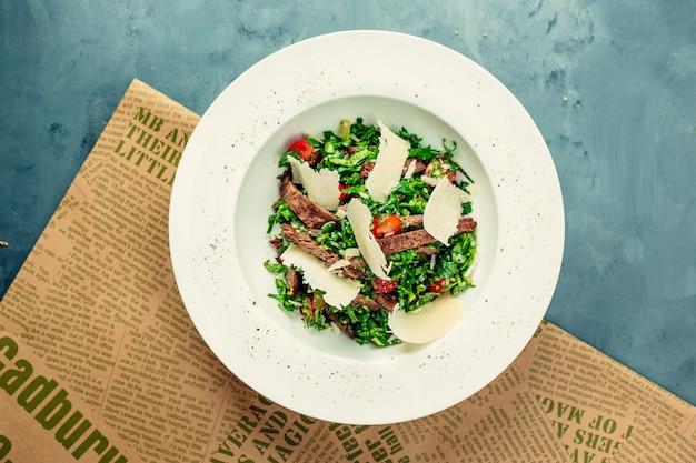 Groene salade met vlees en gehakte kaas in witte kom.