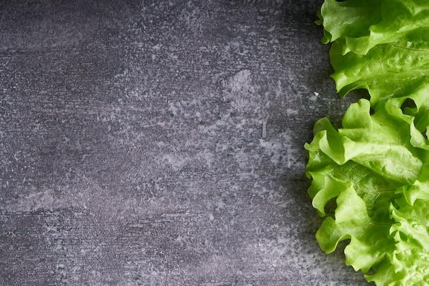 Groene salade op grijze stenen tafel exemplaarruimte
