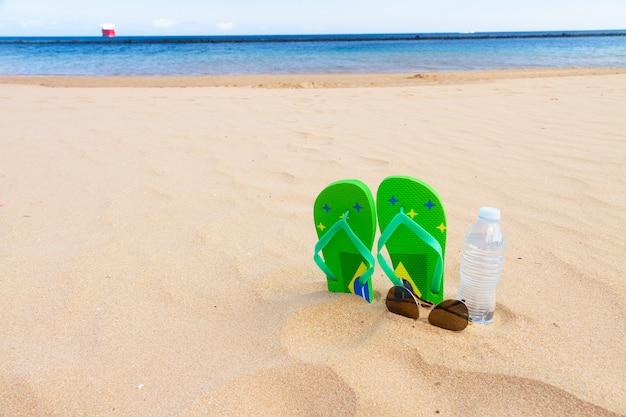 Groene sandalen op strand met een fles helder water en glazen