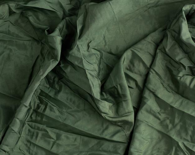 Groene satijnen textielstof, stuk stof voor het naaien van gordijnen en zo