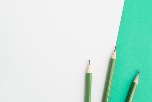 Groene scherpe potloden op dubbele achtergrond