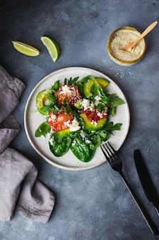Groene slakom met rucola, snijbiet, avocado, bloedsinaasappel, zeezout, cottage cheese geschroeid op keramische plaat op blauwe stenen muur met limoen, servet en vork en mes. gezond eten concept.