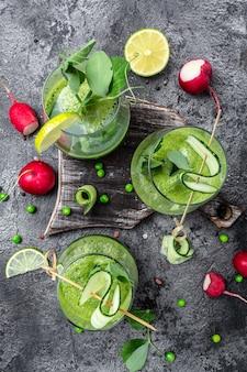 Groene smoothie. detox smoothie, groene verse erwten, komkommer, radijs, spinazie en limoen. verticaal beeld. bovenaanzicht