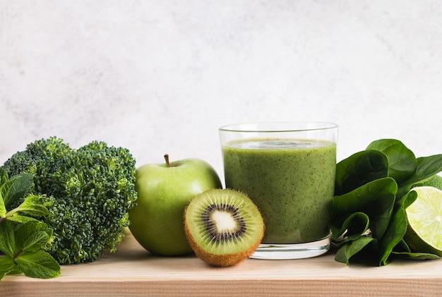 Groene smoothie en ingrediënten op keukentafel
