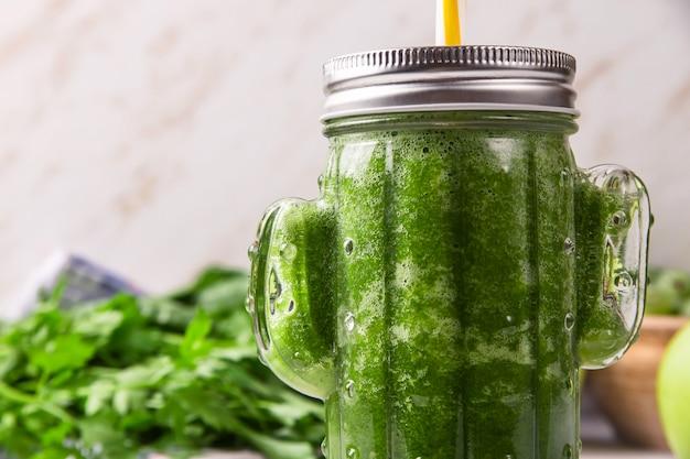 Groene smoothie in een cactusvormig glas tussen de groene ingrediënten