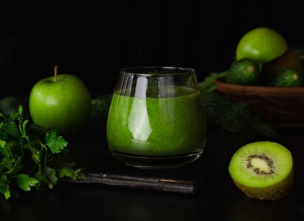 Groene smoothie in een glas glas op een zwarte achtergrond. kiwi, appels, komkommers en groenen. gezond eten koken.