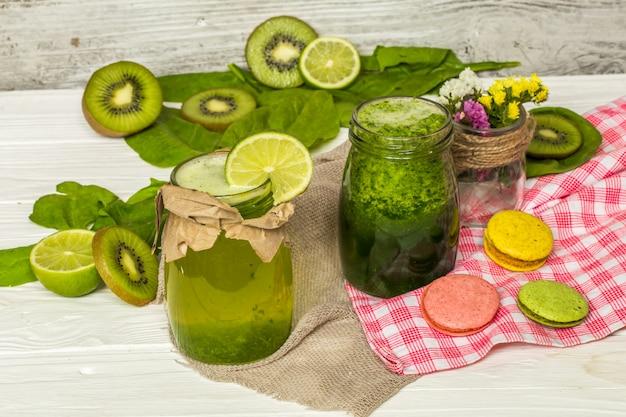 Groene smoothie in een pot met limoen en bessen