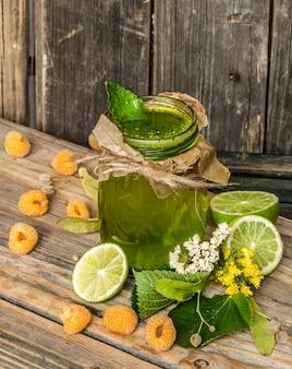 Groene smoothie in een potje met limoen, kiwi en bes