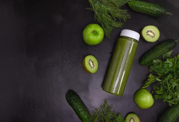 Groene smoothie in een transparante fles op een zwarte achtergrond. de gesneden groenten en fruit liggen klaar. gezond eten, plat gelegd. kopieerruimte.