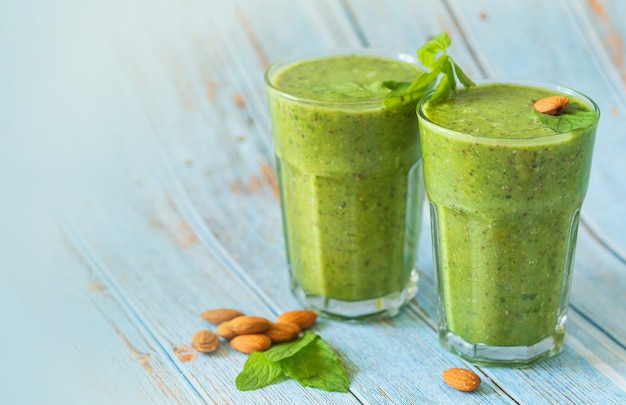 Groene smoothie in glas over blauwe achtergrond, noten, munt met kopieerruimte - detox, vegan, vegetarische gezonde groentedrank