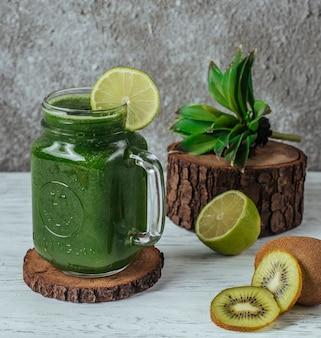 Groene smoothie in metselaarpot met limoenplak, gegarneerd met plakjes kiwi