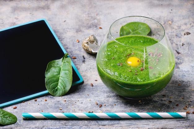 Groene smoothie met appel en bladeren op beton
