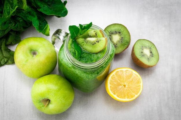 Groene smoothie met spinazie, appel, kiwi en munt in een potmok op grijze steen. het concept van gezonde voeding en dieet. bovenaanzicht.