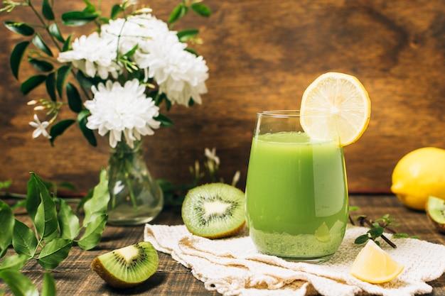 Groene smoothie naast vaas met bloemen