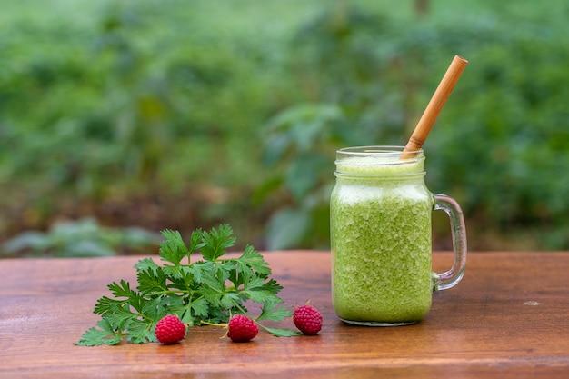 Groene smoothie van peterselie, avocado, honing en banaan in een glazen mok op een houten tafel in een tuin café, close-up. gezond voedselconcept