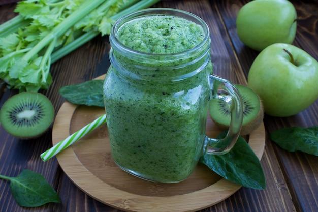 Groene smoothies met groenten en fruit op de houten snijplank