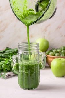 Groene smoothies worden uit een glazen mengkom gegoten