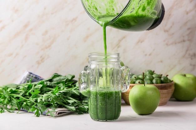Groene smoothies worden uit een glazen mengkom in een glas gegoten