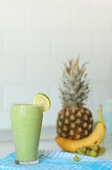 Groene smothie in glas met citroen bovenop, op wazige achtergrond met ananas, banaan en druif, kopieer ruimte bovenaan. gezond