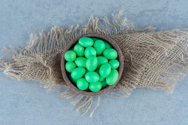 Groene snoepjes in de beker op de onderzetter, op de marmeren tafel.