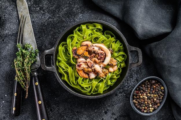 Groene spinazie fettuccine pasta met kaas en zeevruchten, garnalen, inktvis, octopus, mossel. donkere achtergrond. bovenaanzicht.