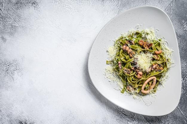 Groene spinazie fettuccine pasta met kaas en zeevruchten, garnalen, inktvis, octopus, mossel. grijze achtergrond. bovenaanzicht. kopieer ruimte.