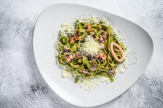 Groene spinazie fettuccine pasta met kaas en zeevruchten, garnalen, inktvis, octopus, mossel. grijze achtergrond. bovenaanzicht.