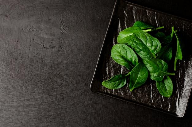 Groene spinazie op zwarte plaat op zwarte achtergrond