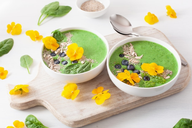 Groene spinazie smoothie kom met bosbessen, chiazaad en eetbare viooltje bloemen