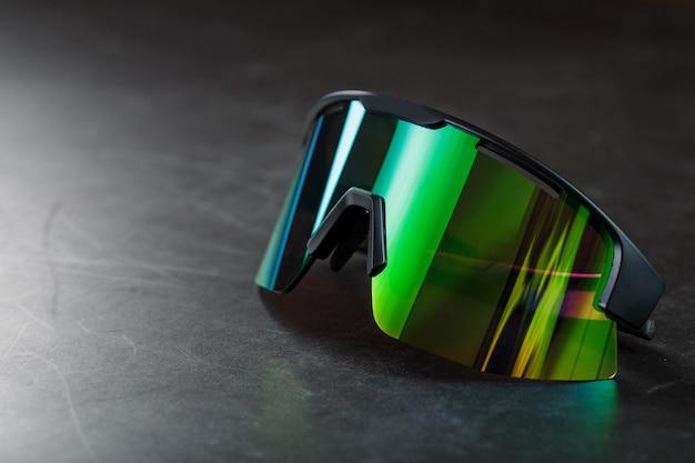 Groene sportbril met een spiegellens op een donkere ondergrond. vrije ruimte