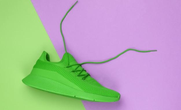 Groene sportsneaker met losgeknoopte veters op een groen-roze papieren ondergrond. creatieve sport stilleven, minimalisme. bovenaanzicht