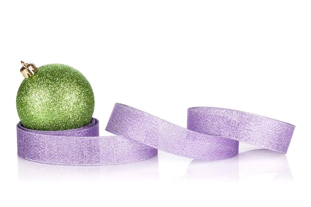 Groene sprankelende kerstbal met paars lint. geïsoleerd op witte achtergrond