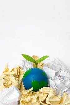 Groene spruit op wereldbol met vuilnis heap